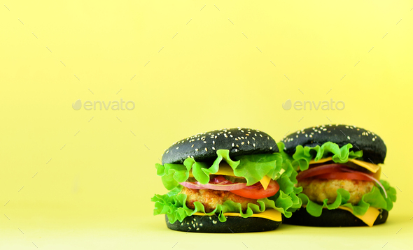 Fast food frame. Delicious meat burgers on yellow background. Take away meal. Unhealthy diet concept - Stock Photo - Images