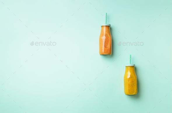 Fresh orange, banana, pineapple, mango smoothies and juicy fruits on blue background. Detox summer - Stock Photo - Images