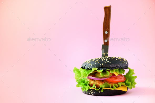 Fast food concept. Juicy black burger with knife on pink background. Take away meal. Unhealthy diet - Stock Photo - Images