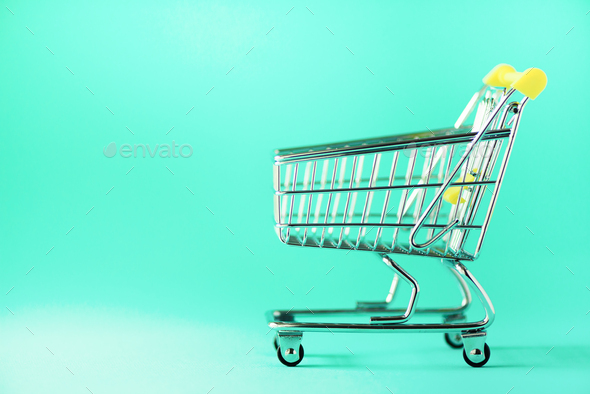 Shopping cart on blue background. Minimalism style. Creative design. Copy space. Shop trolley at - Stock Photo - Images