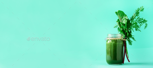Banner of green smoothie with leafy beet greens and carrot tops on blue background, copy space - Stock Photo - Images