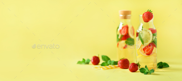 Strawberry detox water with mint, lemon on yellow background. Citrus lemonade. Banner. Summer fruit - Stock Photo - Images