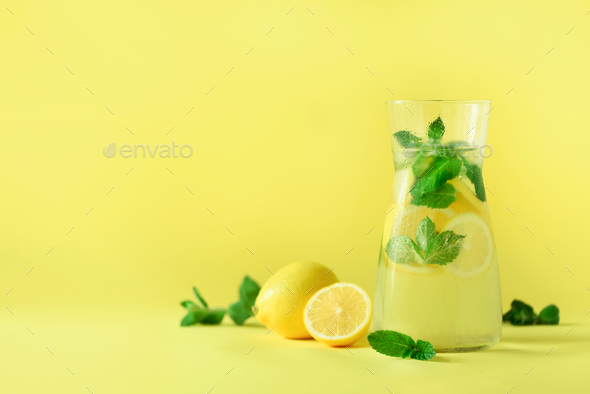Citrus lemonade - cold water with ice, mint, lemon on yellow background. Detox drink. Summer fruit - Stock Photo - Images