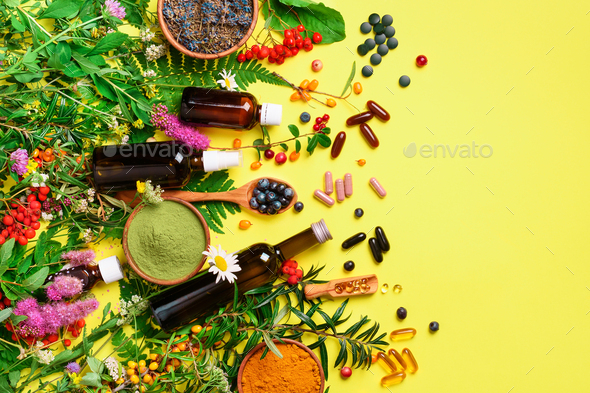 Alternative medicine. Holistic approach. Healing herbs and flowers over yellow background. Top view - Stock Photo - Images