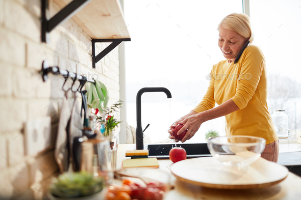 Cheerful woman washing fruit while talking on phone - Stock Photo - Images