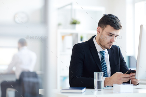 Man texting by workplace - Stock Photo - Images