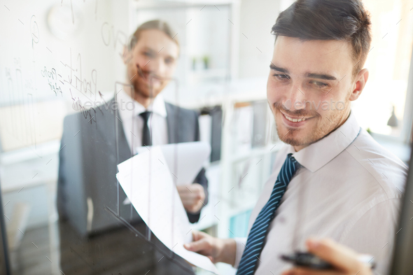 Analyst pointing at data on board - Stock Photo - Images