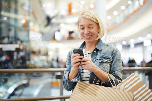 Happy woman texting sms in shopping mall - Stock Photo - Images