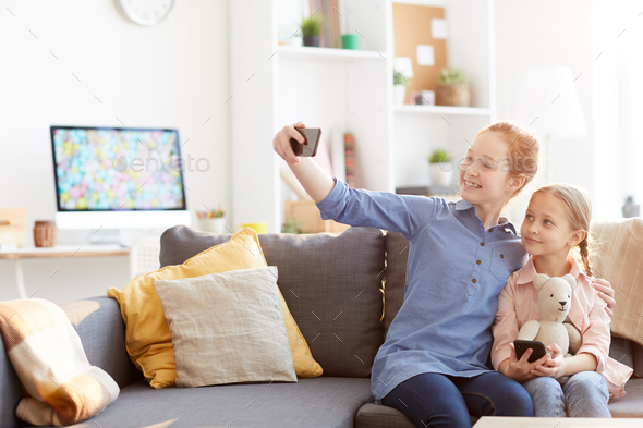 Two Sisters Taking Selfie at Home - Stock Photo - Images