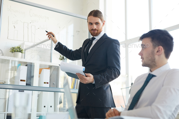 Businessman by whiteboard - Stock Photo - Images
