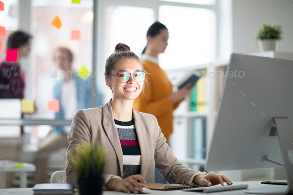 Woman in front of computer monitor - Stock Photo - Images