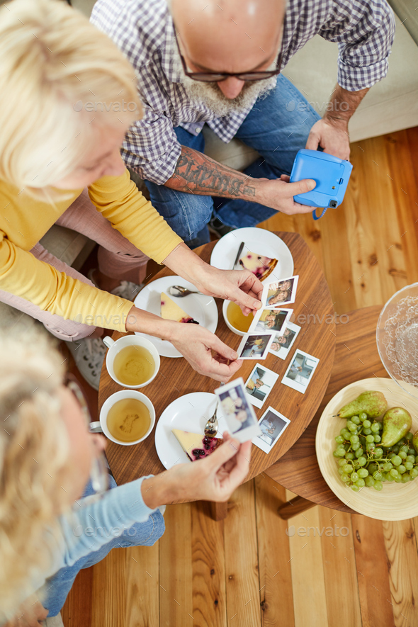 Mature friends watching polaroid images - Stock Photo - Images