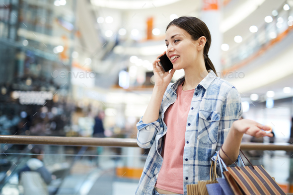 Smiling woman talking on phone in mall - Stock Photo - Images