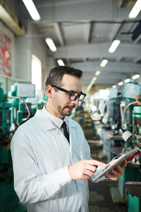Mature Factory Worker Holding Tablet - Stock Photo - Images