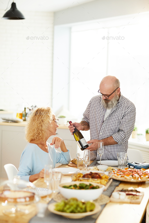 Man showing bottle of wine to girlfriend - Stock Photo - Images