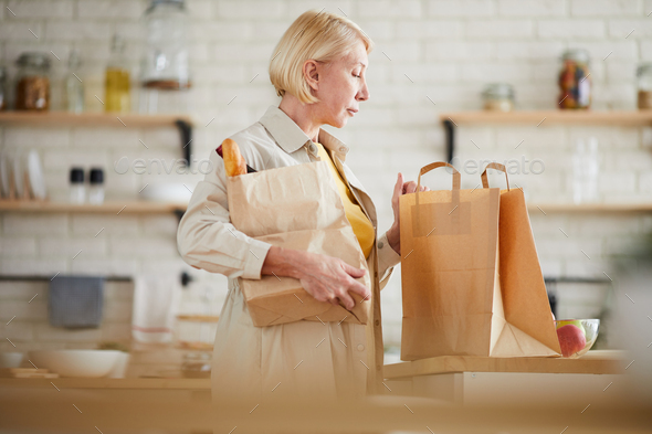 Mature woman coming home after shopping in grocery store - Stock Photo - Images