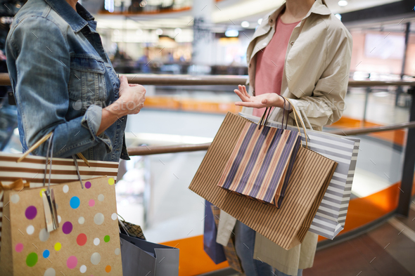 Women discussing purchases in shopping mall - Stock Photo - Images