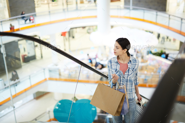 Pretty woman looking around while moving up escalator - Stock Photo - Images