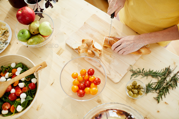 Cutting baguette on wooden board - Stock Photo - Images