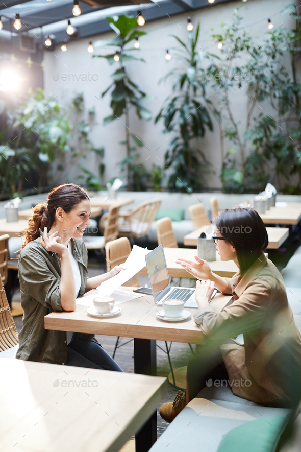 Positive women analyzing report in cafe - Stock Photo - Images