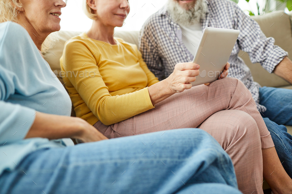 Aged friends watching video on tablet - Stock Photo - Images