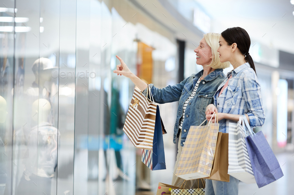 Cheerful mother and daughter discussing clothing of mannequins - Stock Photo - Images