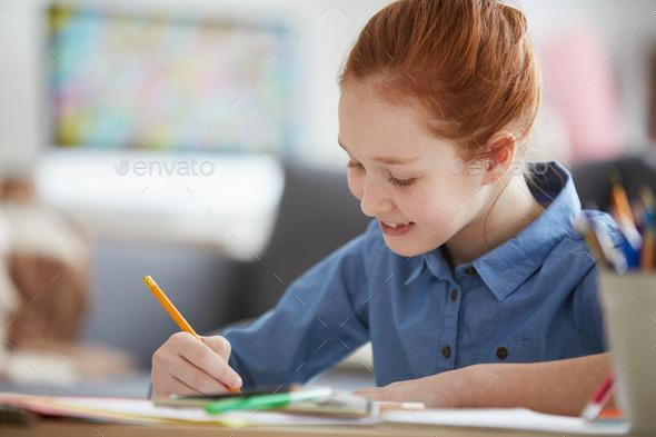 Red Haired Girl doing Homework - Stock Photo - Images