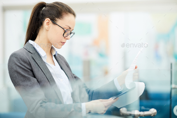Businesswoman Reading Document - Stock Photo - Images