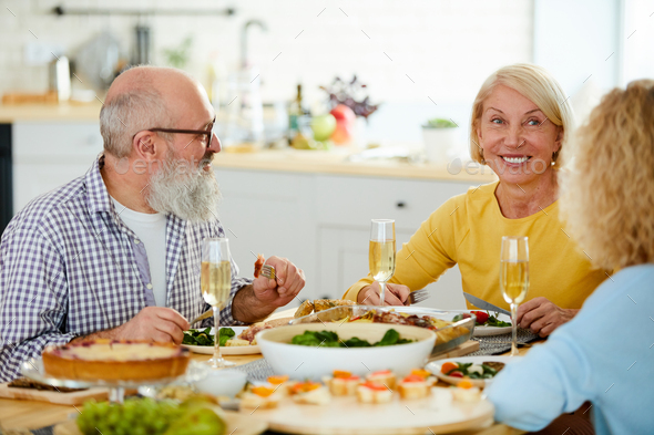 Happy mature friends having dinner together - Stock Photo - Images