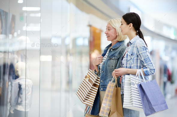 Mother and daughter looking at clothing through window of shop - Stock Photo - Images