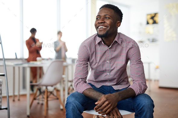 African-American Man Sitting on Chair - Stock Photo - Images