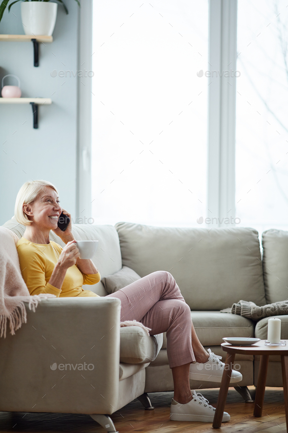 Woman talking on phone in living room - Stock Photo - Images