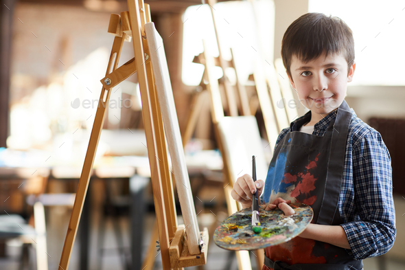 Cute Little Boy Posing by Easel - Stock Photo - Images