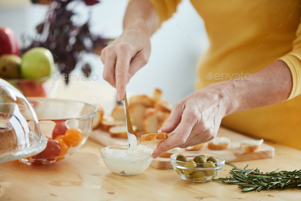 Buttering bread with knife - Stock Photo - Images