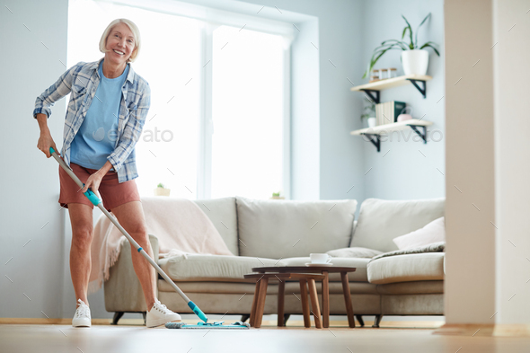 Cheerful woman washing floor at home - Stock Photo - Images
