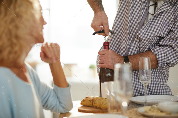 Using corkscrew to open wine bottle - Stock Photo - Images