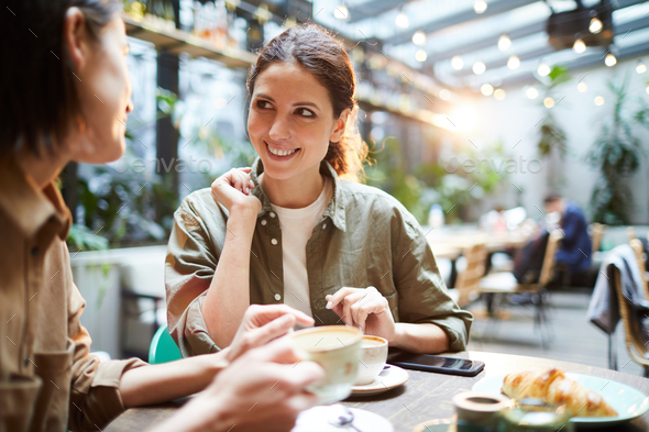 Positive women discussing last news in cafe - Stock Photo - Images