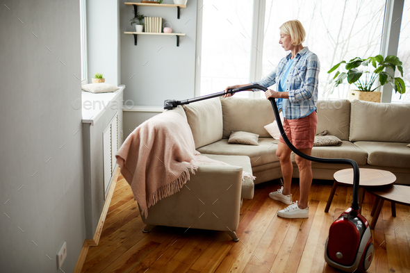 Woman using vacuum cleaner - Stock Photo - Images