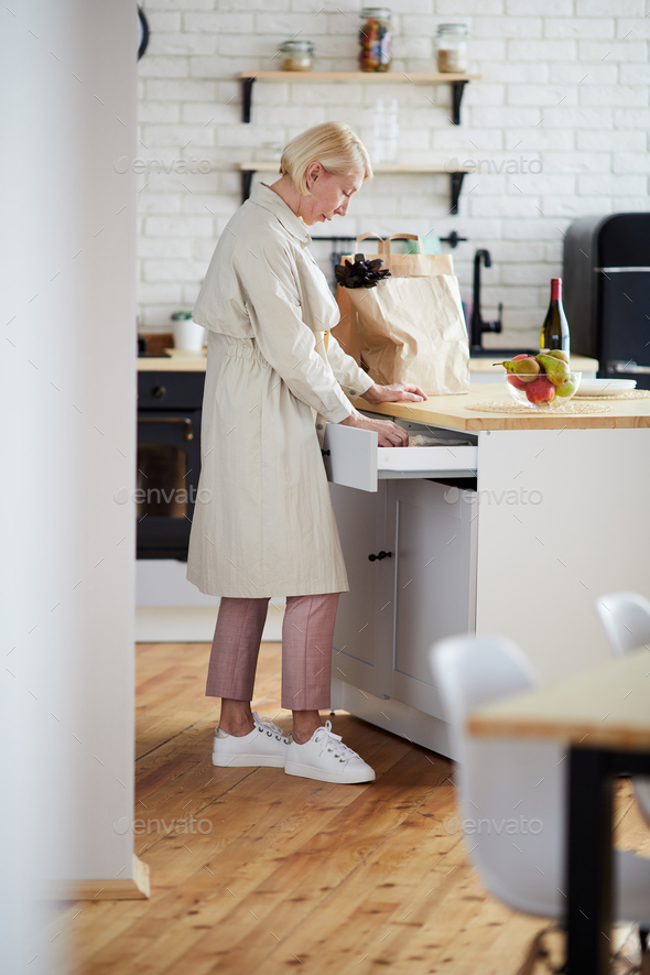 Woman finding utensil in kitchen drawer - Stock Photo - Images