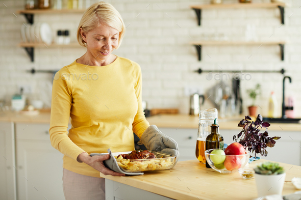 Mature woman taking hot dish out of oven - Stock Photo - Images