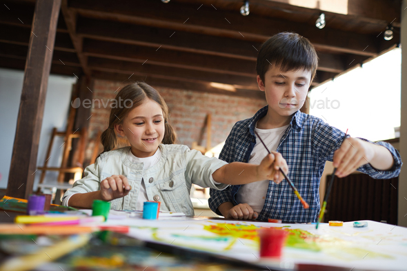 Two Siblings Painting Together - Stock Photo - Images