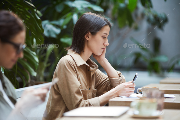 Puzzled woman examining article in cafe - Stock Photo - Images