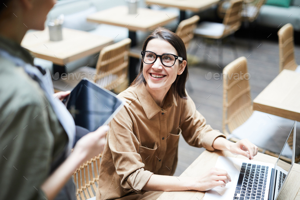Happy freelance lady ordering drink in cafe - Stock Photo - Images