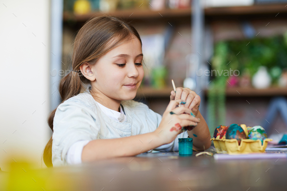 Girl Painting Eggs for Easter - Stock Photo - Images