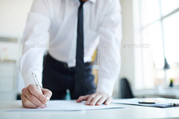 Putting signature on paper - Stock Photo - Images
