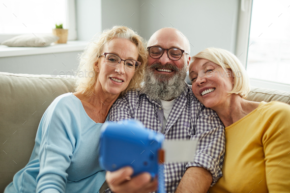 Excited mature friends taking selfie on instant camera - Stock Photo - Images