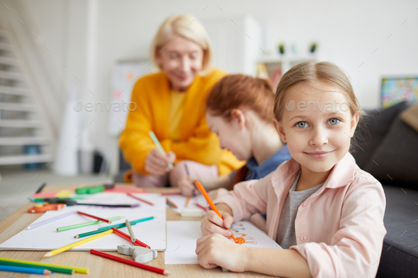 Cute Girl Looking at Camera while Drawing - Stock Photo - Images