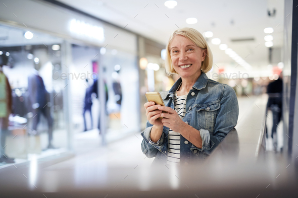 Sales consultant of clothing store texting sms during break - Stock Photo - Images
