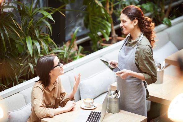Lady asking waitress about dessert - Stock Photo - Images