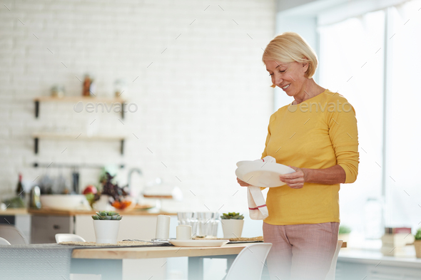 Mature woman wiping plate with dish towel - Stock Photo - Images